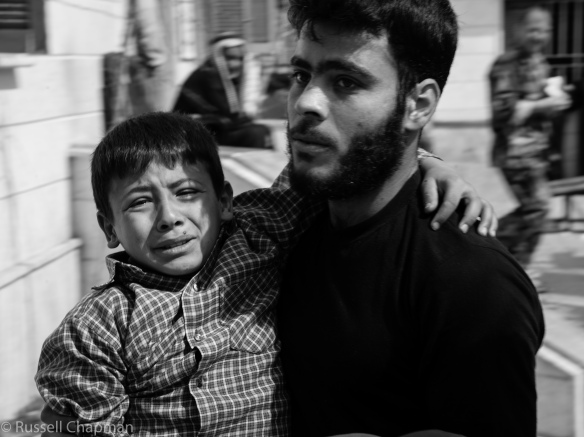 This boy was injured by shrapnel. His father is rushing him to a field hospital